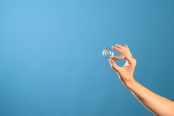 The idea, the creation of innovations, the concept. A small vintage incandescent lamp in a female hand, blue background.