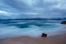 The idyllic Number Sixteen Beach with an incoming storm at dusk in Rye, Victoria, Australia