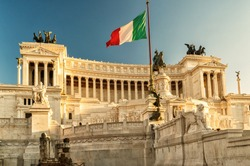 The II Vittoriano building with the flag on Piazza Venezia at sunset, Rome, Italy. It is one of the main travel destinations of Italy. Sunny view of the Italian flag on Capitol. Postcard of Italy.