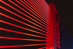 The illuminated structure of the Seri Saujana Bridge at night. One of many bridges in Putrajaya, Malaysia, all alternately illuminated in unison in different colors. Putrajaya Bridge Malaysia at night