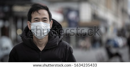 The image face of a young Asian man wearing a mask to prevent germs, toxic fumes, and dust. Prevention of bacterial infection Corona virus or Covid 19 in the air around the streets and gardens.