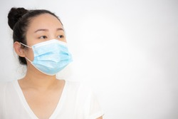 The image face of a young Asian woman wearing a mask to prevent germs, toxic fumes, and dust. Prevention of bacterial infection Corona virus or Covid 19  in a white background.