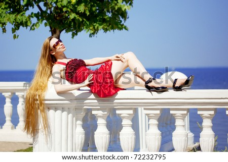 The image of a beautiful girl in the red dress on the beach #72232795