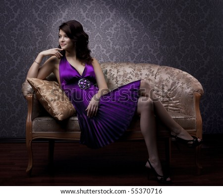 The image of a beautiful luxurious woman sitting on a gold vintage couch - stock photo