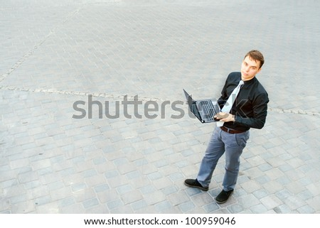 The image of a businessman working on the computer and standing in the middle of the street