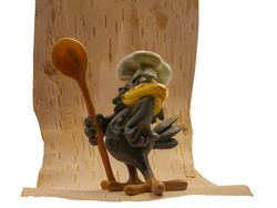 The image of a confectionery product in the form of a stylized figure of a crow on a birch bark background. On the head is a chef's hat. Holds a spoon. The figurine is covered with glaze.