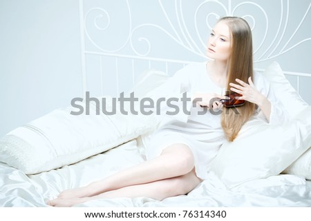 The image of a girl combing her hair in bed