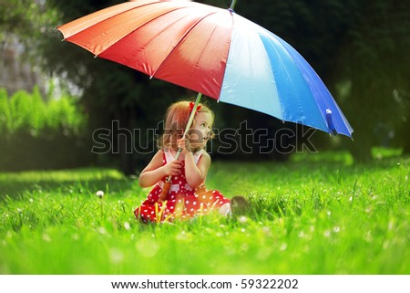 The image of a little girl with a rainbow umbrella in park