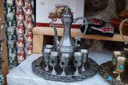 The image of a vintage silver jar and six silver small wine glasses on a tray. Jar and wine glasses service. Vintage dishware.