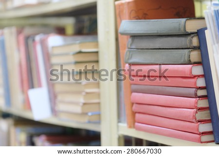 The image of books on the shelf in a library. The books on the background are blurred
