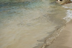 The image of brown mud on a beach is a reflection of the filthiness and negligence of man that has damaged nature.