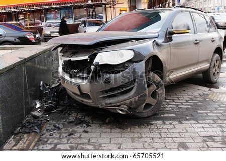 The image of crashed car stands on a sidewalk