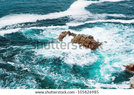 The image of stormy waves lapping on the small stone isle. Against the backdrop of bright white foam stands emerald water.