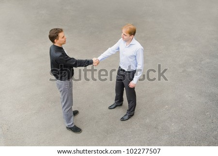 The image of the business partners concluding a bargain. Focus is made on top of the gray background of the empty street.