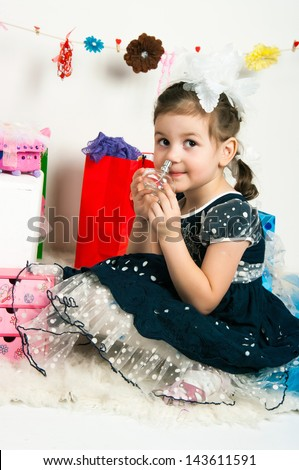 The image of the elegant girl playing with cosmetics and jewelry