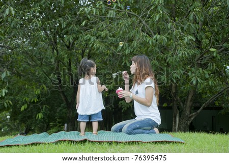 The image of the girl puts the bubbles in the park with her mother,mother day