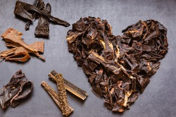 The image of the Heart is laid out from treats for dogs. Natural dried treats for dogs on a dark background. Treats for motivation at dog shows and training. Pet care. Pet supplies. Selective focus.