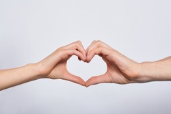 The image of the heart, taken by two young white hands, male and female, is covered with a white background. The concept of love, together forever, support.