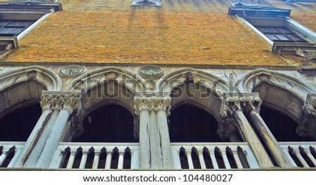 The image of the house bright sand color with the balcony in the style of Venice, Italy.