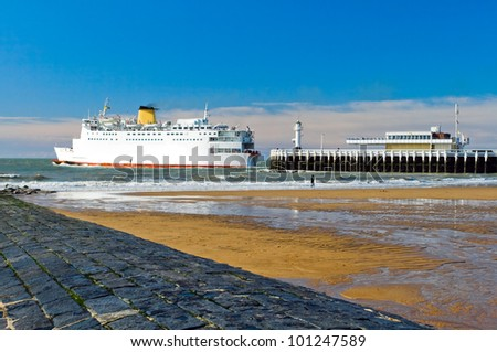 The image of the pier, where a big ship sailing from Ostend.