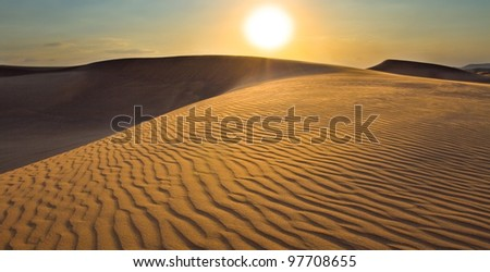 The image of the sunset with many sandy dunes in a safari in Dubai