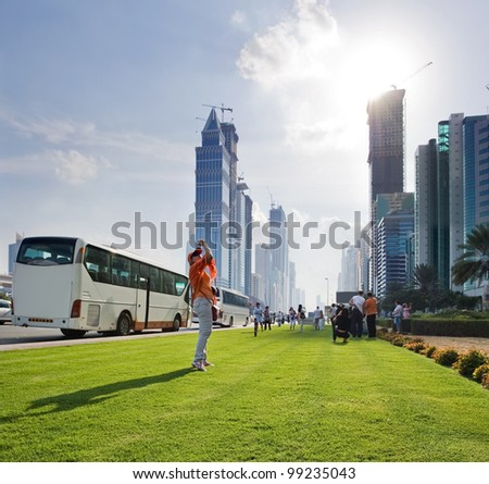 The image of tourists taking pictures of skyscrapers, many of which are still under construction. The whole street is filled with tourist buses in the afternoon. - stock photo