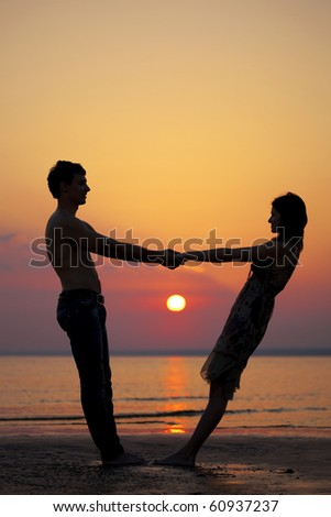 The image of two people in love at sunset - stock photo