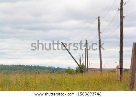 The image shows a series of electric poles in which one of the poles has rotted, bent and hangs on wires, against a background of grass, sky and forest.