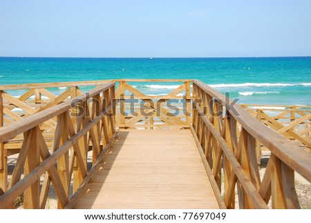 the image shows a wooden bridge at the beach