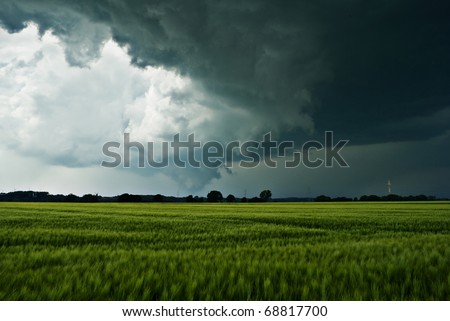 The image shows dark rainclouds over a field (barley) and was taken a few minutes after a small tornado. I'm not sure, but I think you can see the rest of the tornado.