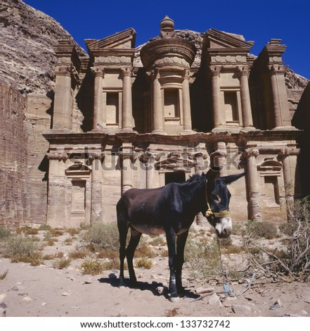 The imposing Monastery in Petra, Jordan with at foreground a donkey.