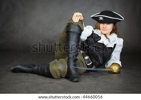 The impudent woman the pirate lies with a sabre on a black background