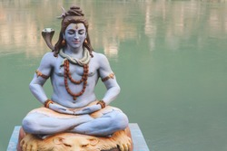 The Indian God Shiva meditates against the backdrop of the waters of the Ganges River.