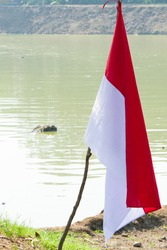 The Indonesian flag,  red and white flag is tied to a tree branch and is flown on the edge of the lake
