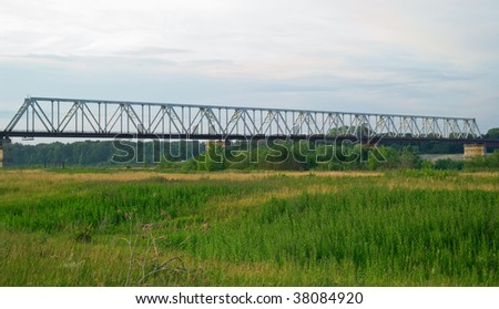 The industrial bridge through the river against the sunset evening sky
