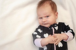 The infant baby on white background. Black bodysuit with white hearts. The emotion of anger. Cunning newborn.