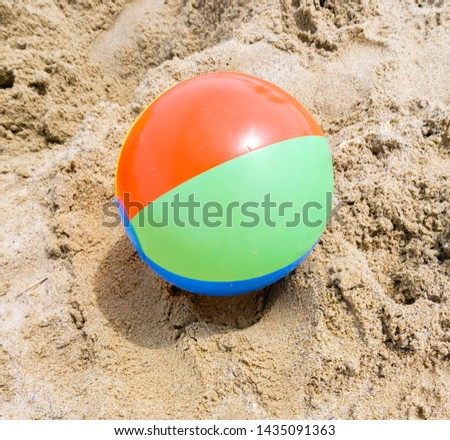 The inflatable ball at beach lies on the beach without people. Shallow depth of field, soft focus, selective focus. #1435091363