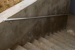 The infrastructure of town houses. Concrete staircase to the basement of a residential building with metal railings. The concept of construction and putting into operation of residential buildings.