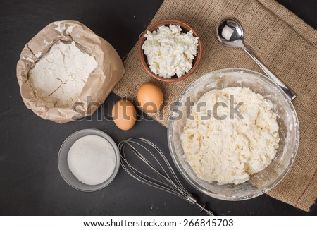 The ingredients for homemade cheesecake: curd in ceramic bowl, two eggs, sugar in a glass bowl, whisk,  wheat flour in a paper bag, iron spoon, wheat flour mixed with butter, on sacking, top view #266845703