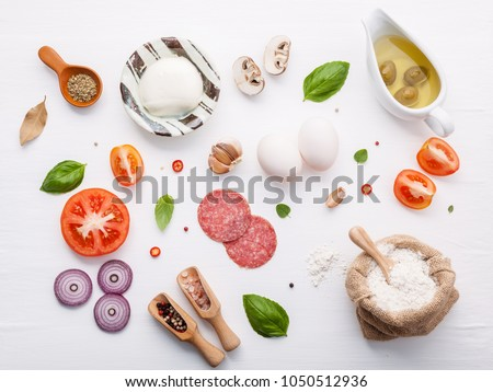 The ingredients for homemade pizza with ingredients sweet basil ,tomato ,garlic ,bay leaves ,pepper ,onion and mozzarella cheese on white wooden background with flat lay.