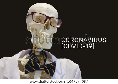The inscription Coronavirus COVID-19 and the human skeleton in a white coat with a bow in glasses on a black background.