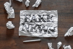 The inscription - fake news, on a piece of crumpled paper. The concept is a means of propaganda, the media, a means of manipulating the public.