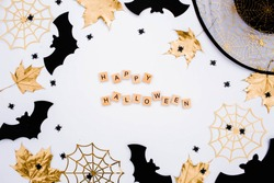 The inscription happy Halloween. Modern background with black bats, Golden leaves, cobwebs and wooden letters.  Halloween with copy space for text. Flat lay, top.