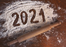 the inscription 2021 is handwritten on flour on a wooden table with a rolling pin next to it. new year concept.