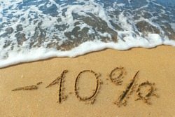The inscription minus ten percent on the sand near the ocean. Discount on vacation at the sea.