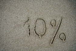 The inscription minus ten percent on the sand near the ocean. Discount on vacation at the sea. -10%. inscription on the sand minus 10 percent