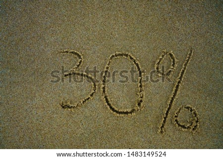 The inscription minus thirty percent on the sand near the ocean. Discount on vacation at the sea. -30% #1483149524