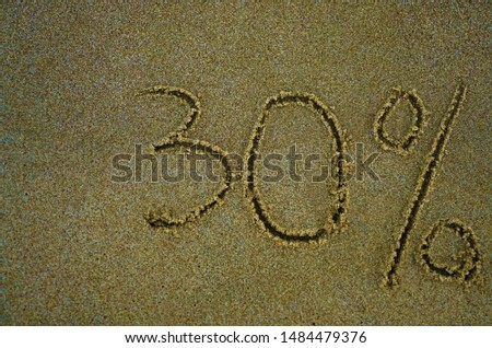 The inscription minus thirty percent on the sand near the ocean. Discount on vacation at the sea. -30% #1484479376