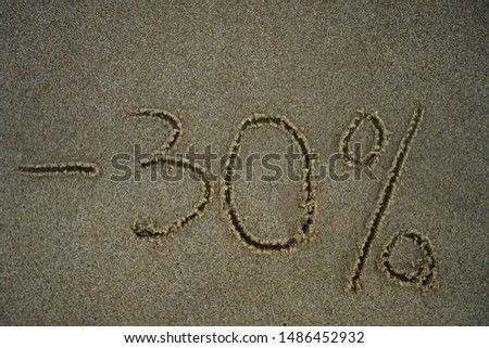The inscription minus thirty percent on the sand near the ocean. Discount on vacation at the sea. -30% #1486452932