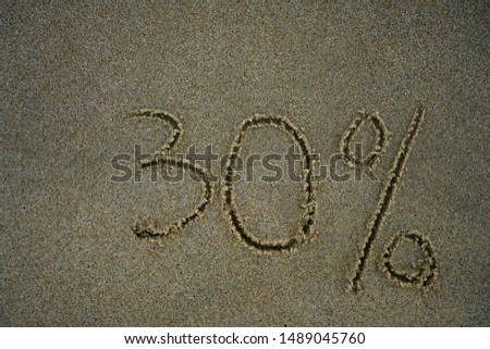 The inscription minus thirty percent on the sand near the ocean. Discount on vacation at the sea. -30% #1489045760